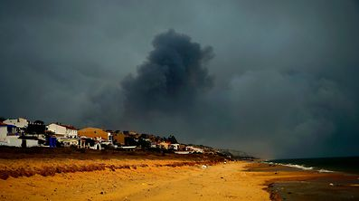 A picture taken on July 25, 2017 from the beach shows smoke billowing in Mazagon, next to the Donana National Park. More than 1,500 people were evacuated as a precaution on June 25, 2017 after a fire broke out at a nature reserve in southern Spain famed for its biodiversity. The fire started overnight and had by morning encroached on the Donana National Park at Moguer in the southern region of Andalusia, Jose Fiscal, deputy head of the regional environment protection authority, told Spanish television.  / AFP PHOTO / CRISTINA QUICLER