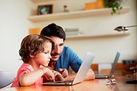 Mid adult man assisting son in using laptop at table