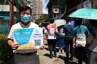 """This photo taken on July 11, 2020 shows a volunteer (L) holding up a sign as people (R) queue to vote for New Territory East candidates during a primary election in Hong Kong. - China on July 14, 2020 has described a primary by Hong Kong's pro-democracy parties as a """"serious provocation"""", warning that some campaigning may have breached a tough new security law it imposed on the city. (Photo by May JAMES / AFP)"""