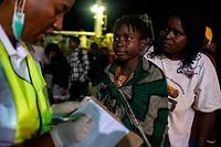 An aid worker writes down the names of a woman and a child after they arrived on a fishing vessel at the port in Beira, on March 22, 2019. - Members of the Indian Navy together with aid workers has set up a triage and medical centre at the port in Beira to help people who have been displaced in Buzi, as a result of Tropical Cyclone Idai. Aid workers faced disarray, a clamour for help and mounting anger on March 22 as they headed out across central Mozambique, struggling to help tens of thousands of people battered by one of southern Africa's most powerful storms. A week after Tropical Cyclone Idai lashed Mozambique with winds of nearly 200 kilometres (120 miles) per hour, rescue efforts rose a gear but the situation was often chaotic. (Photo by WIKUS DE WET / AFP)