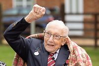 """TOPSHOT - A handout picture released on April 30, 2020 shows Captain Tom Moore waving at a flypast by Battle of Britain Memorial planes to celebrate his 100th birthday in Marston Moretaine. (Photo by Emma SOHL / CAPTURE THE LIGHT / AFP) / RESTRICTED TO EDITORIAL USE - MANDATORY CREDIT """"AFP PHOTO / CAPTURE THE LIGHT / EMMA SOHL"""" - NO MARKETING NO ADVERTISING CAMPAIGNS - DISTRIBUTED AS A SERVICE TO CLIENTS --- NO ARCHIVE ---"""