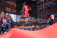 Arbeiter rollen den Teppich für die 70. Filmfestspiele vor dem Berlinale Palast aus.