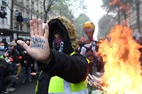 """A protester holds up his hand with """"Macron get out"""" written on his palm as he stands next to burning objects in the street during the annual May Day (Labour Day) rally in Paris on May 1, 2021. (Photo by Alain JOCARD / AFP)"""