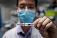 """(FILES) In this file photo taken on April 29, 2020, an engineer shows an experimental vaccine for the COVID-19 coronavirus that was tested at the Quality Control Laboratory at the Sinovac Biotech facilities in Beijing. - Sinovac Biotech is conducting one of the five clinical trials of potential vaccines that have been authorised in China. China would make any coronavirus vaccine it developed a """"global public good"""" once it was put into use, President Xi Jinping told the World Health Assembly on May 18, 2020. (Photo by NICOLAS ASFOURI / AFP)"""