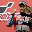 MotoGP class winner Ducati rider Andrea Dovizioso of Italy holds a victory trophy on the podium during the MotoGP Japanese Grand Prix at Twin Ring Motegi circuit in Motegi, Tochigi prefecture on October 15, 2017. / AFP PHOTO / TOSHIFUMI KITAMURA