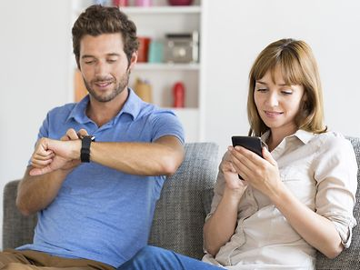 Digital geek couple. Mobile phone, smartwatch. Modern white apartment