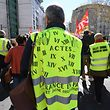 A demonstrator (C) wearing a yellow vest (gilet jaune) on which is written all the previous yellow vest protests,  takes part in a 'Day of strikes' called by French workers' unions to demand more purchasing power and to defend public services, on March 19, 2019 in Montpellier. (Photo by Pascal GUYOT / AFP)