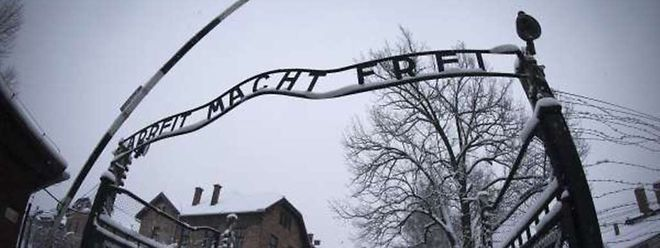 """Au-dessus de la porte d'entrée du camp, on peut lire: """"Arbeit macht frei"""" (""""le travail rend libre"""")."""