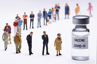 """This photograph taken on January 4, 2021 in Paris, shows figurines next to a vaccine vial reading  """"Covid-19 vaccine"""".,Image: 580850526, License: Rights-managed, Restrictions: , Model Release: no"""