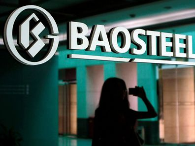 A woman is reflected on a wall with a company logo of Baosteel Group at an office in Shanghai, July 24, 2011.   REUTERS/Stringer/File Photo    CHINA OUT. NO COMMERCIAL OR EDITORIAL SALES IN CHINA