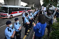 Police line up as pro-democracy supporters show signs for pro-democracy activists Agnes Chow, Ivan Lam and Joshua Wong outside the court in Hong Kong on Decemberber 2, 2020, after the three were sentenced after pleading guilty to inciting a rally during pro-democracy protests in 2019, deepening the crackdown against Beijing's critics. (Photo by Peter PARKS / AFP)