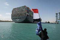 HANDOUT - 29.03.2021, Ägypten, Suez: Ein Arbeiter schwenkt eine Flagge Ägyptens, während im Hintergrund das Containerschiff «Ever Given» in Begleitung von Schleppern über den Suezkanal fährt. Nach tagelanger Blockade durch das riesige Containerschiff ist der Suezkanal wieder frei. Die «Ever Given» wurde am Nachmittag wieder vollständig flottgemacht, wie das Bergungsunternehmen Boskalis mitteilte. Foto: -/Suez Canal Authority/dpa - ACHTUNG: Nur zur redaktionellen Verwendung und nur mit vollständiger Nennung des vorstehenden Credits +++ dpa-Bildfunk +++