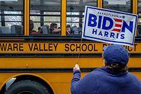 28.10.2020, USA, Milford: Eine Frau hält ein Biden-Plakat neben einem Schulbus in die Höhe. Die Präsidentschaftswahl in den USA findet am 03. November 2020 statt. Foto: Preston Ehrler/SOPA Images via ZUMA Wire/dpa +++ dpa-Bildfunk +++