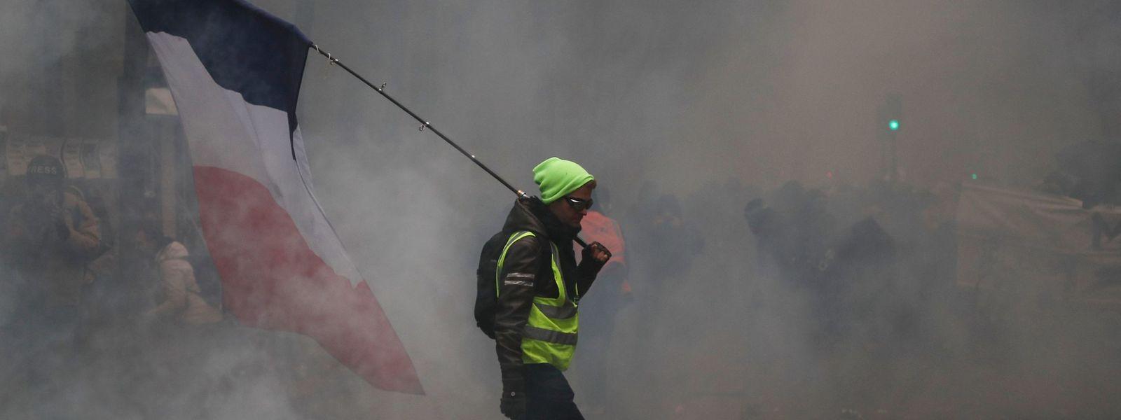 Ein Mann mit einer gelben Weste und einer französischen Flagge bei der Demonstration am Donnerstag.