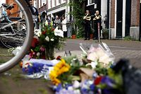 """Bystanders including security personnel look at a display of flowers, candles and messages of support for Peter R. de Vries in the Lange Leidsedwarsstraat, central Amsterdam on July 7, 2021, after the crime reporter was seriously injured after an attempt on his life late July 6. - Prominent Dutch crime reporter Peter R. de Vries was fighting for his life in a Dutch hospital on July 7, 2021, after being shot multiple times, including in the head, in what the EU chief described as  """"an attack on our values."""" Amsterdam police chief Frank Paauw said three people had been arrested, among them the suspected shooter, but gave no details on the possible reasons for the attack. (Photo by Koen van Weel / ANP / AFP) / Netherlands OUT"""