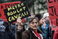 A protestor holds a sign that reads in French, 'Subway, job, cellar' during a demonstration on day 36 of a nationwide multi-sector strike over French government's plan to overhaul the country's retirement system in Nantes, western France on January 9, 2020. - The French President's push for sweeping changes to the pension system has unleashed the longest transport strike in France in decades, causing weeks of travel chaos in the French capital Paris particularly. (Photo by Sebastien SALOM-GOMIS / AFP)