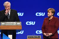 (FILES) In this file photo taken on November 20, 2015, Horst Seehofer, then Bavarian State Premier and party leader of the Christian Social Union Party (CSU), and German Chancellor Angela Merkel stand on the stage during a CSU party congress in Munich, southern Germany. As German Chancellor Angela Merkel fights to save her government in a heated battle over immigration, a poll showed on June 15, 2018 most Germans support the tougher line of her rebel interior minister. The survey found that 62 percent were in favour of turning back undocumented asylum seekers at the border, in line with the stance of Interior Minister Horst Seehofer who is openly challenging Merkel. / AFP PHOTO / Christof STACHE