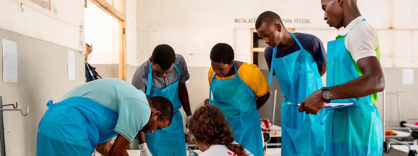 Katrien Duquet, Ärztin von der Hilfsorganisation Ärzte ohne Grenzen, kümmert sich im Cholerabehandlungszentrum mit Gesundheitsfachkräften und der mosambikanischen Ärztin Violinda (3.v.r.) um ein an Cholera erkranktes Kind.