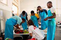 04.04.2019, Mosambik, Mar Azul: Katrien Duquet, Ärztin Hilfsorganisation Ärzte ohne Grenzen, kümmert sich im Cholerabehandlungszentrum mit Gesundheitsfachkräften und der mosambikanischen Ärztin Violinda (3.v.r.) um ein an Cholera erkranktes Kind.  Die Zahl der Cholerafälle nach dem verheerenden Zyklon «Idai» in Mosambik ist nach neuen Zahlen auf fast 2100 gestiegen. Foto: Pablo Garrigos/Ärzte ohne Grenzen /dpa - ACHTUNG: Nur zur redaktionellen Verwendung im Zusammenhang mit der aktuellen Berichterstattung und nur mit vollständiger Nennung des vorstehenden Credits +++ dpa-Bildfunk +++