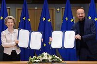 European Commission President Ursula von der Leyen (L) and European Council President Charles Michel (R) pose in Brussels, on December 30, 2020 as they show the signed Brexit trade agreement due to come into force on January 1, 2021. - EU leaders Ursula von der Leyen and Charles Michel signed Wednesday the post-Brexit trade deal agreed with Britain, in a brief ceremony. The texts were then to be flown to London in an RAF jet for the signature of Prime Minister Boris Johnson, on the eve of Britain's departure from the EU single market. (Photo by JOHANNA GERON / POOL / AFP)