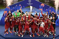 Liverpool's players celebrate with the trophy after winning the UEFA Champions League final football match between Liverpool and Tottenham Hotspur at the Wanda Metropolitan Stadium in Madrid on June 1, 2019. (Photo by ANTONIN THUILLIER / AFP)