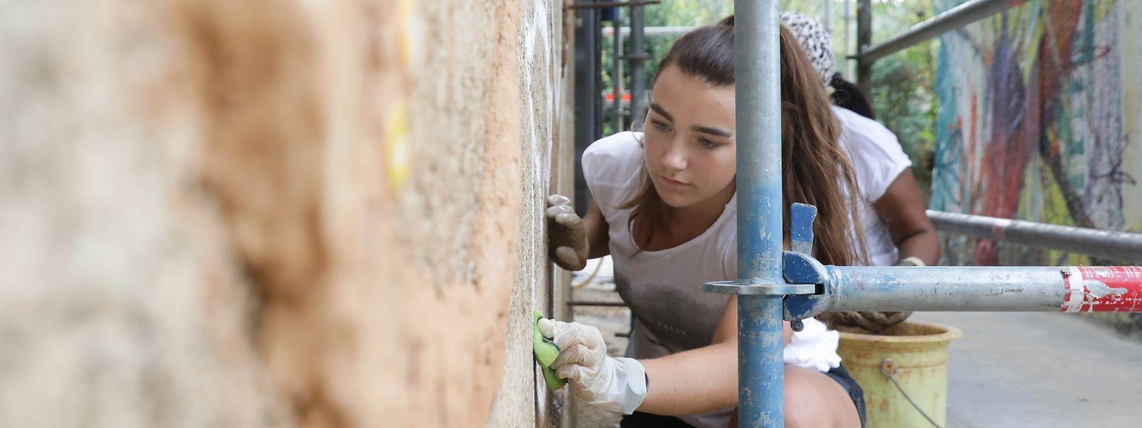 Freiwillige helfen derzeit die Fassade des Benu-Village an der Escher Grenz zu schmücken.