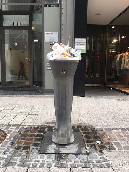 """Gerade in den Fußgängerzonen kommt es regelmäßig vor, dass die Wasserspender als Mülltonnen missbraucht werden. Diese Aufnahme stammt vom Tag des Stroossemaart. Bei dem Spender handelt es sich um die moderne Variante, das Modell """"O'claire""""."""