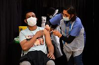 A health worker gives an injection of the Astrazeneca/Oxford Covid-19 vaccine at a temporary vaccination centre set up at the East London Mosque in London on April 14, 2021. (Photo by JUSTIN TALLIS / AFP)