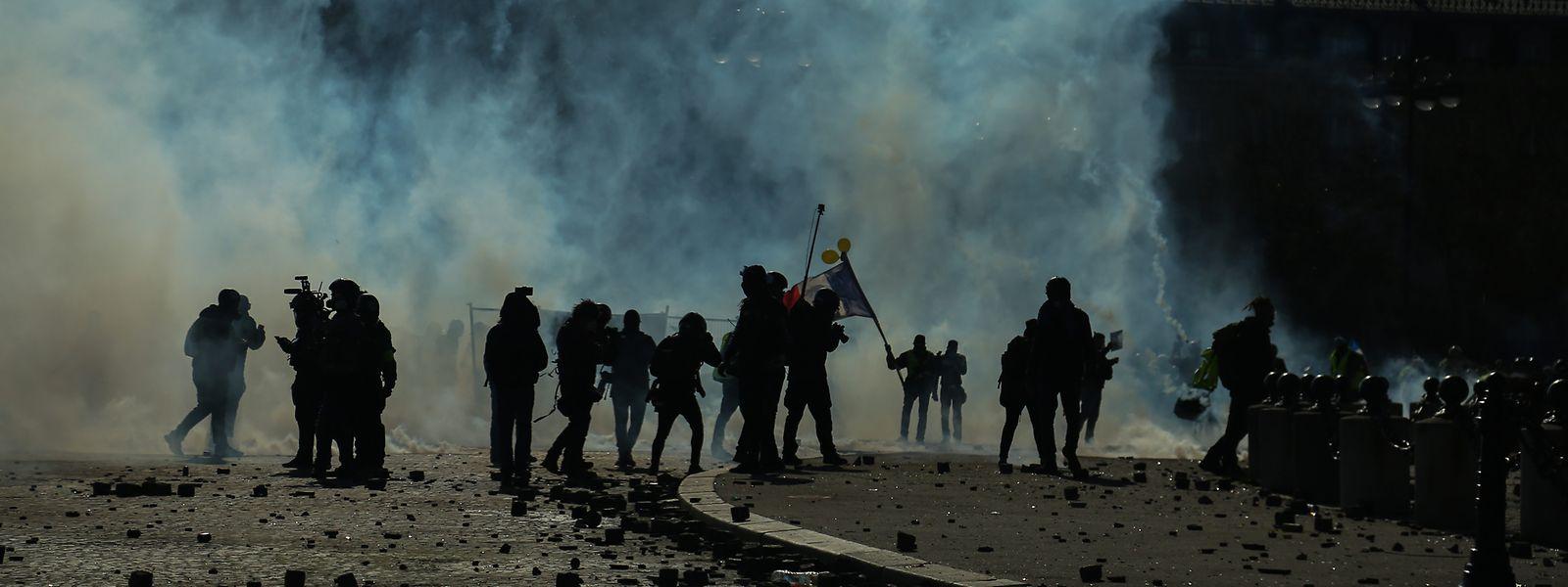 Bereitschaftspolizisten und Demonstranten sind in Rauchschwaden gehüllt.