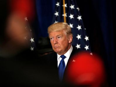 Republican presidential nominee Donald Trump reacts as reporters yell questions to him after he stated that he believes US President Barack Obama was born in the US at a campaign event at the Trump International Hotel in Washington, D.C.