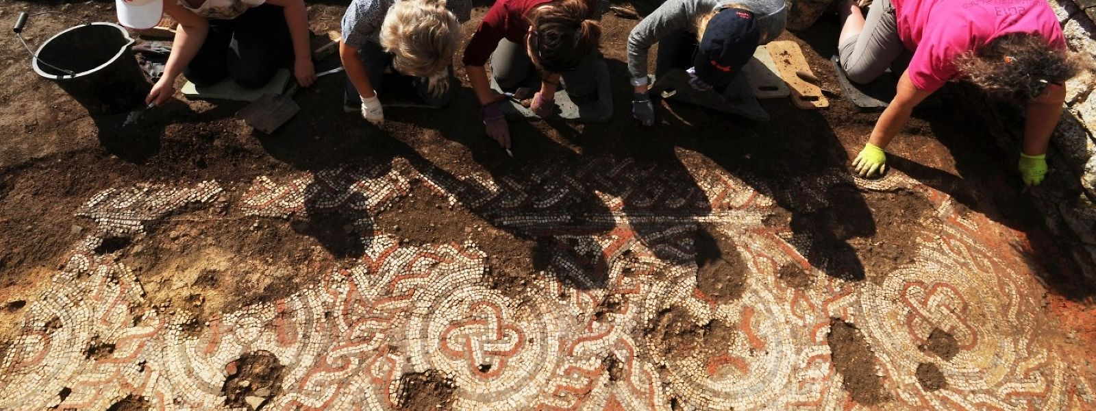 Archäologen legen ein Mosaik frei, das bei Ausgrabungsarbeiten des National Trust an einer römischen Villa in Chedworth entdeckt wurde.