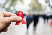 closeup of a red awareness ribbon for the fight against AIDS in the hand of a young caucasian man in a busy pedestrian street of a city