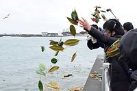 People throw leaves into the sea to commemorate 2011 tsunami disaster in Soma, Fukushima Prefecture on March 11, 2019. - On March 11, 2011 a devastating 9.0-magnitude quake struck under the Pacific Ocean and the resulting tsunami caused widespread damage and claimed thousands of lives. (Photo by JIJI PRESS / JIJI PRESS / AFP) / Japan OUT