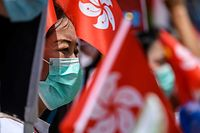 Pro-China supporters display Chinese and Hong Kong flags during a rally near the government headquarters in Hong Kong on June 30, 2020, as China passed a sweeping national security law for the city. - China passed a sweeping national security law for Hong Kong, a historic move that critics and many western governments fear will smother the finance hub's freedoms and hollow out its autonomy. (Photo by Anthony WALLACE / AFP)