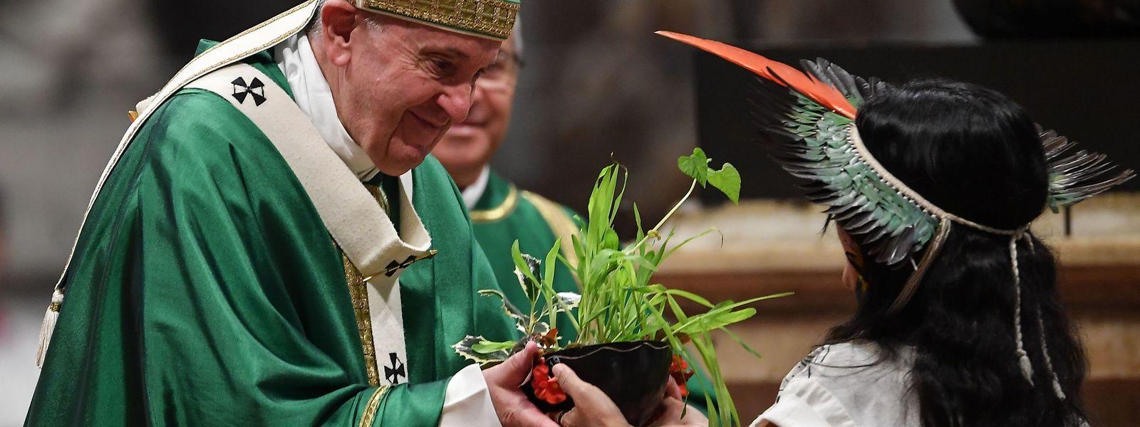 Papst Franziskus erhält während der Schlussmesse im Peterdsdom eine Pflanze einer Indigenen-Vertreterin