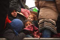 Syrian women and children sit in the back of a truck on a road near the town of al-Ghazawiya as they flee pro-regime attacks on the western countryside of Aleppo, to seek refuge in safer areas near the Turkish border on February 11, 2020. - Regime and Russian forces have intensified their attacks on the rebel-held areas of the northern Aleppo province, with government forces closing in on a two-kilometre section of the M5 highway that remains outside of their control. The key motorway connects Damascus to second city Aleppo and is economically vital to the government after nine-years of war. (Photo by AAREF WATAD / AFP)
