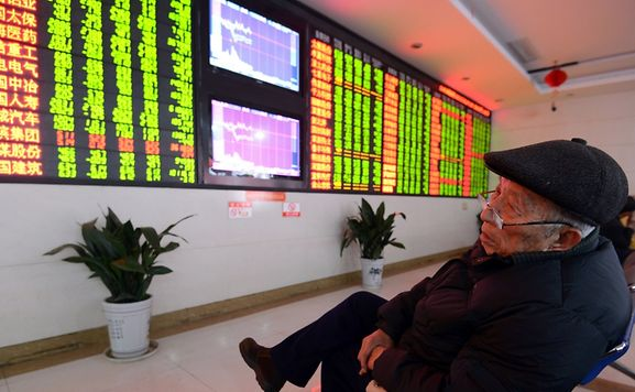 An investor sits in front of a screen showing stock market movements in a stock firm in Fuyang, east China's Anhui province on Monday. Trading on the Shanghai and Shenzhen stock exchanges was ended early on January 4 after shares fell seven percent.