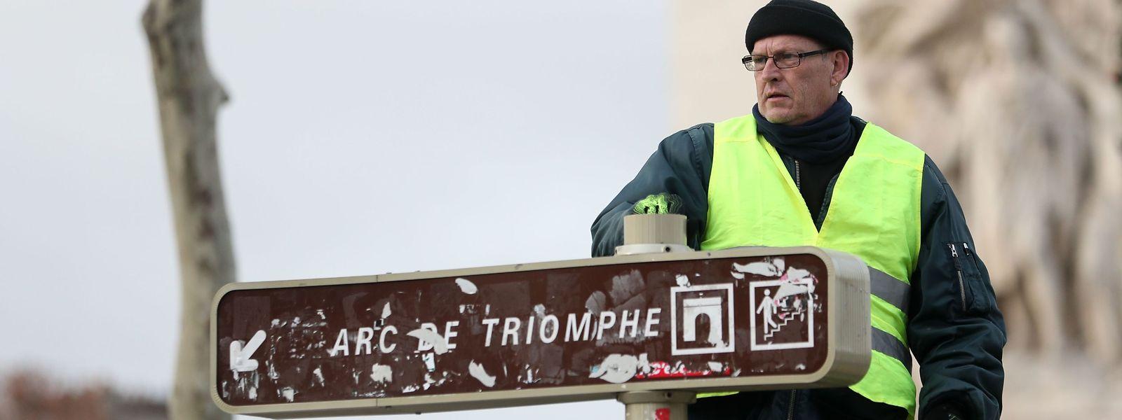 """Un manifestant s'est hissé sur un panneau indiquant la direction de l'Arc de Triomphe à Paris, devenu un symbole pour les """"gilets jaunes""""."""