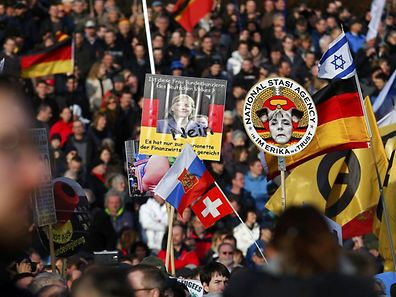 Supporters of the anti-Islam movement Pegida hold posters depicting German Chancellor Angela Merkel during a demonstration in Dresden on Saturday.