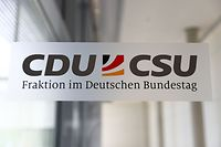 """A sign in the corridors of the Parliament compound reads """"CDU/CSU parliamentary group"""", on July 2, 2018 in Berlin. German Chancellor Angela Merkel of the conservative Christian Democratic Union (CDU) and her Interior Minister Horst Seehofer of the CDU's Bavarian sister party CSU are expected to meet later in the day in a final bid to resolve differences over migration policy threatening to rip apart Germany's ruling coalition. / AFP PHOTO / Omer MESSINGER"""