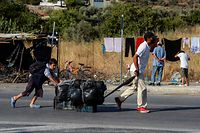 Migrants walk with their belongings along a road near a temporary camp on September 17, 2020 in Lesbos as Police began an operation to rehouse thousands of homeless migrants at a new site after their camp was destroyed by fire last week. (Photo by Manolis LAGOUTARIS / AFP)