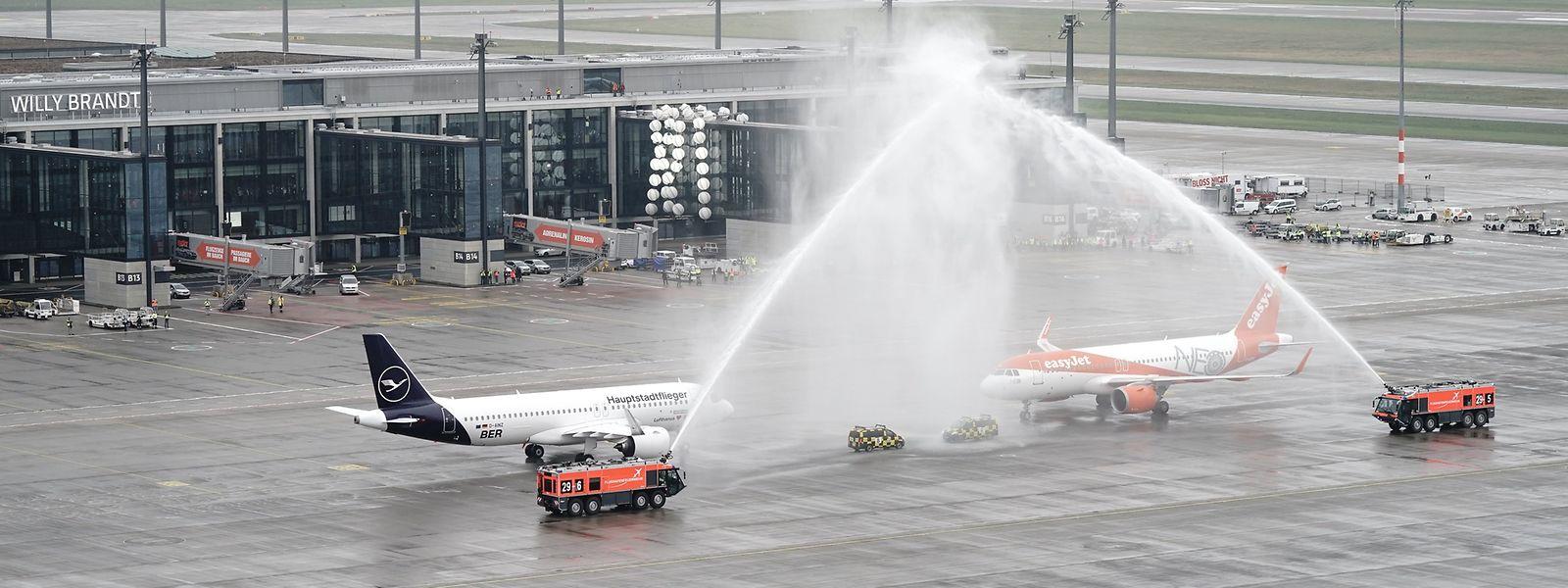 Flugzeuge der Fluggesellschaften Lufthansa und Easyjet stehen nach der Landung unter einer Wasserfontäne der Flughafen-Feuerwehr.