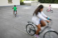 Im Schulhof des Lycée des Arts et Métiers üben Kinder auf spielerische Art und Weise das Fahrradfahren.