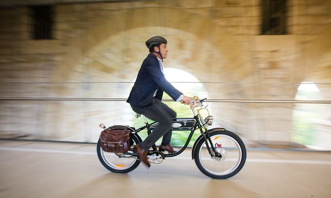 A cyclist passes through Luxembourg City on an electric bike