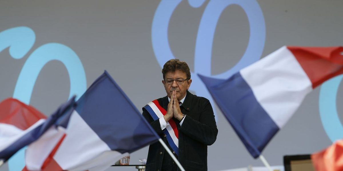 Jean-Luc Melenchon gestures as he speaks on stage during a protest over the government's labour reforms place de la Republique in Paris on September 23, 2017. The third in a series of nationwide protests comes a day after French President signed his signature reforms into law using a fast-tracked procedure that avoided a lengthy parliamentary debate. / AFP PHOTO / GEOFFROY VAN DER HASSELT