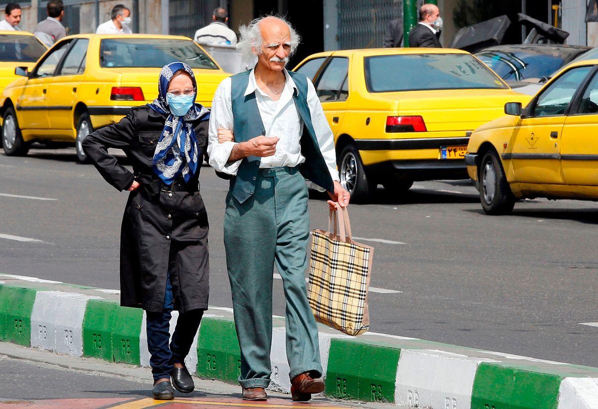 Ein älterer Mann und eine Frau mit Schutzmaske in Teheran.