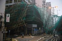 TOPSHOT - A woman uses her umbrella as she walks past collapsed bamboo scaffolding hanging from a building during Super Typhoon Mangkhut in Hong Kong on September 16, 2018. - Typhoon Mangkhut rocked Hong Kong en route to mainland China on September 16, injuring scores and sending skyscrapers swaying, after killing at least 30 people in the Philippines and ripping a swathe of destruction through its agricultural heartland. (Photo by Anthony WALLACE / AFP)