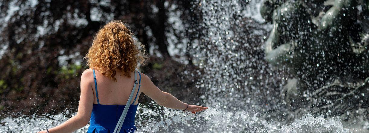15.06.2019, Sachsen, Dresden: Nina aus Dresden läuft durch einen Brunnen am Albertplatz um sich abzukühlen. Foto: Robert Michael/dpa-Zentralbild/dpa +++ dpa-Bildfunk +++