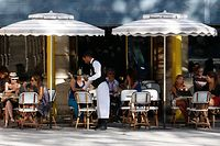 """(FILES) In this file photo taken on August 23, 2016 in Paris, people sit on the outside sitting area of a cafe by the Jardin du Palais Royal. French """"bistrots"""" apply to be declared World Heritage of Humanity by UNESCO in 2020, AFP reported on June 8, 2018. / AFP PHOTO / MATTHIEU ALEXANDRE"""