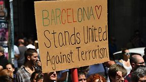 A person holds a placard before observing a minute of silence for the victims of the Barcelona attack at Plaza de Catalunya on August 18, 2017, a day after a van ploughed into the crowd, killing 13 persons and injuring over 100 on the Rambla in Barcelona. Drivers have ploughed on August 17, 2017 into pedestrians in two quick-succession, separate attacks in Barcelona and another popular Spanish seaside city, leaving 13 people dead and injuring more than 100 others. In the first incident, which was claimed by the Islamic State group, a white van sped into a street packed full of tourists in central Barcelona on Thursday afternoon, knocking people out of the way and killing 13 in a scene of chaos and horror. Some eight hours later in Cambrils, a city 120 kilometres south of Barcelona, an Audi A3 car rammed into pedestrians, injuring six civilians -- one of them critical -- and a police officer, authorities said. / AFP PHOTO / Pascal GUYOT